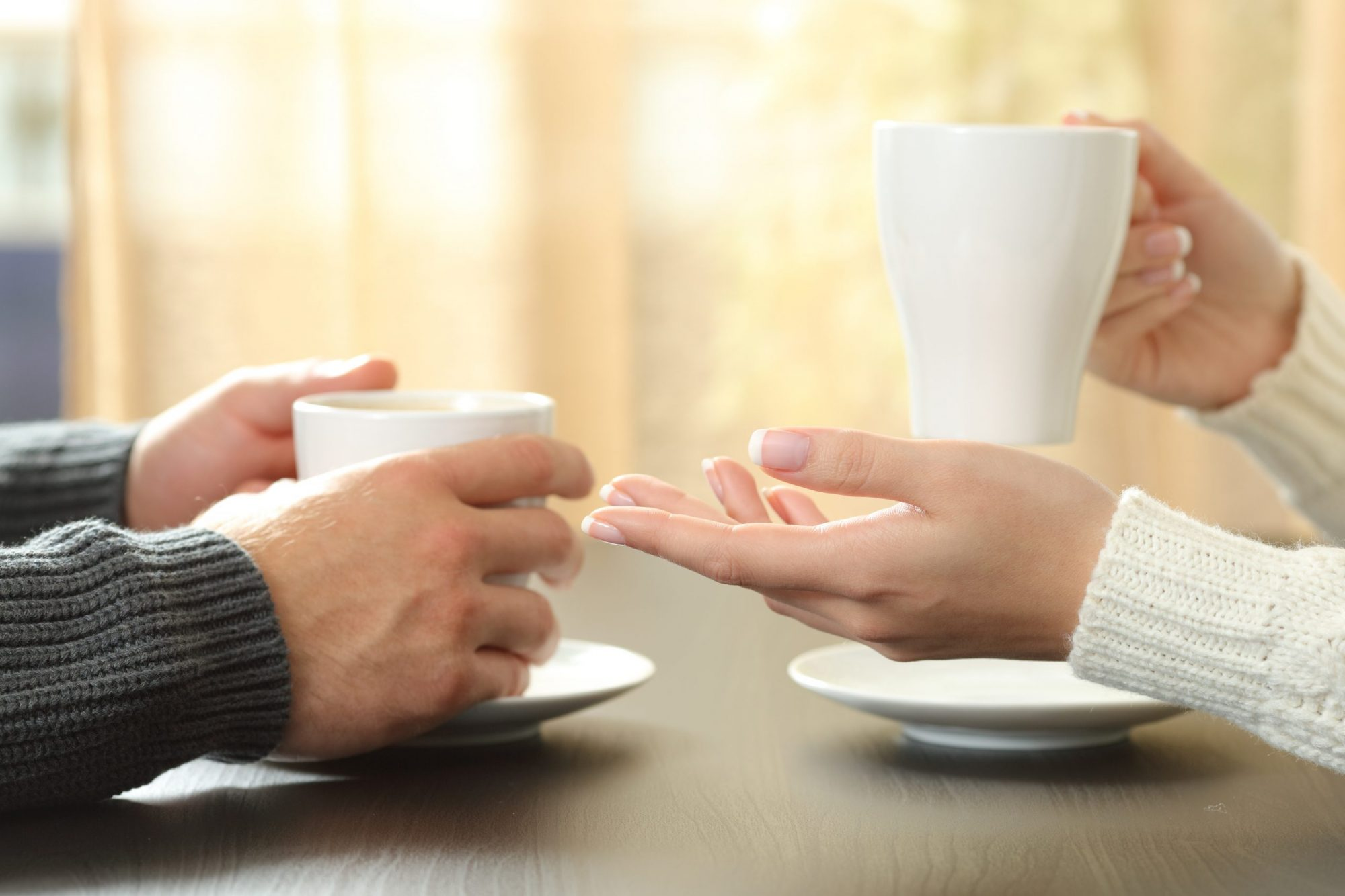 A couple holding coffee cups at table, if deciding to end marriage, meet with a top rated Elmhurst divorce attorney.